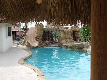 rock coping around pool roof top waterfall and slide with custom spa - Cool Pools With Caves